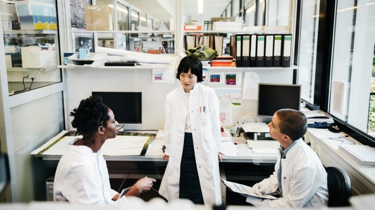Three female scientists discussing their research